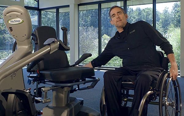 Tom mit NuStep und Rollstuhl