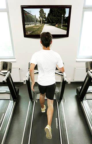 Spoteee mit trainierendem Mann auf Laufband